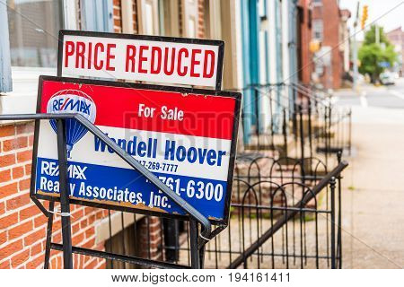 Harrisburg USA - May 24 2017: Pennsylvania capital city houses with Re Max for sale price reduced sign in downtown by sidewalk street
