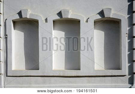 The facade of a white building with some imaginary windows. Geometric stucco on the facade of the building. Evening shadows on the wall.