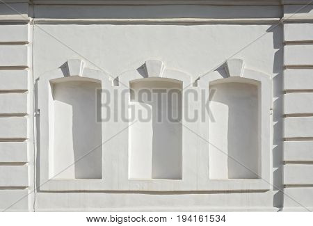The facade of a white building with three imaginary windows. Geometric stucco on the facade of the building. Evening shadows on the wall.