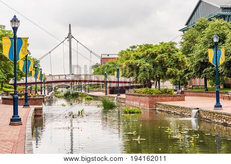 Frederick USA - May 24 2017: Carroll Creek in Maryland city park with canal reflection and people walking by bridge with sign