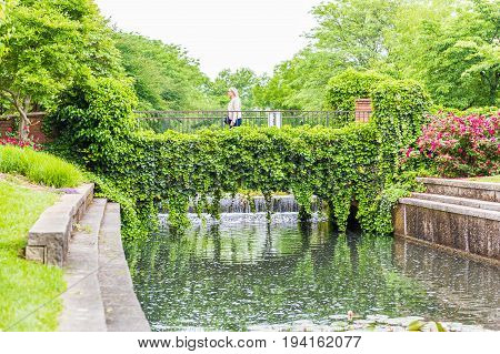Frederick USA - May 24 2017: Carroll Creek in Maryland city park with canal reflection and people walking on bridge