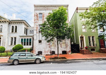 Frederick USA - May 24 2017: Maryland downtown city with entrance door to old white brick house and sidewalk with cars in residential neighborhood