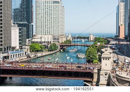 Chicago USA - May 30 2016: View of Wacker Drive with bridges skyscrapers people and cars in downtown