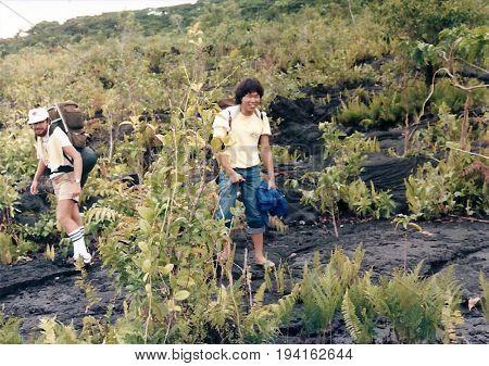 SAVAI'I / SAMOA - CIRCA 1990: American tourists with backpacks explore a lava field.