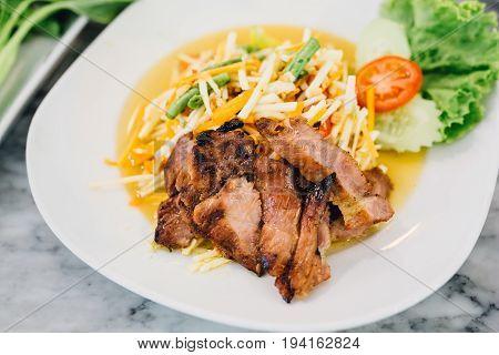 Papaya Salad with Grilled Pork Neck on white plant.