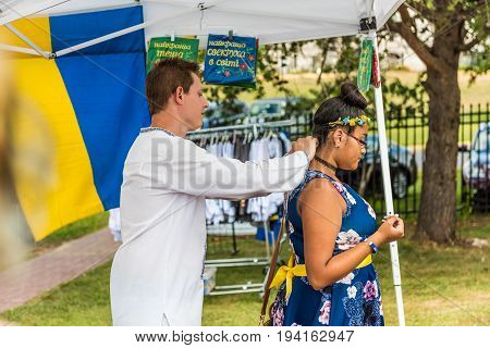Silver Spring USA - September 17 2016: Girl buying Ukrainian beauty flower decorations with man dressed in traditional red Ukrainian embroidered costume clothes