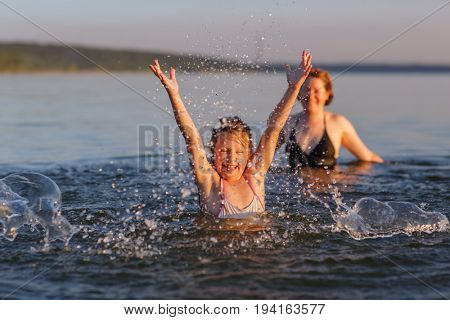 A little girl and her mother are engaged in a fun charging in the water of the sea.