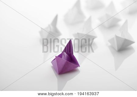 Paper boats on white background. Concept of leadership. Studio shot