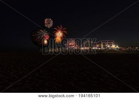 Santa Monica CA USA - July 4 2017: Colorful explosion of fireworks over the Santa Monica Pier over the roller coaster amusement park. Editorial Use Only