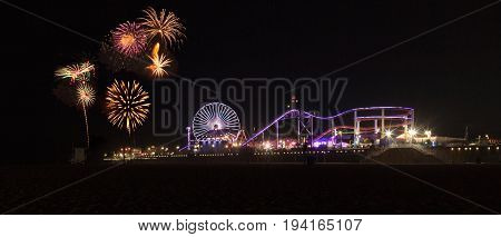 Santa Monica CA USA - July 4 2017: Colorful explosion of fireworks over the Santa Monica Pier over the roller coaster amusement park. Editorial Use Only.