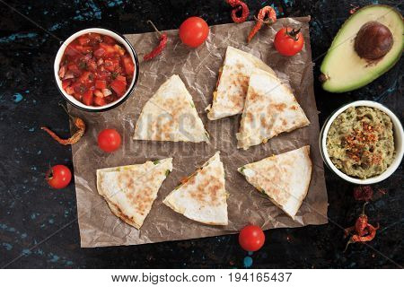 Mexican quesadillas, cheese filled tortilla slices wit salsa and guacamole