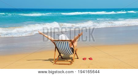 Happy woman in white sunhat on the morning beach sitting on deckchair with hands up.Vacation and travel concept.