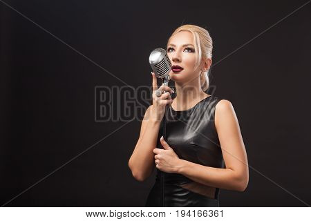 Young blond woman in black leather dress holds a metal microphone in hands. Isolated black background.