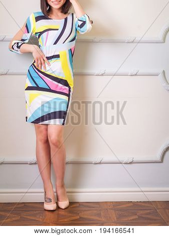 Attractive brunette female with straight beautiful hair in short dress with geometric background posing in classic style room. Hand on the belt