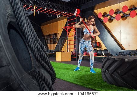 Young athletic woman hitting a hammer on an automobile tire in the gym. Background: gym large car tires gangway horizontal rack