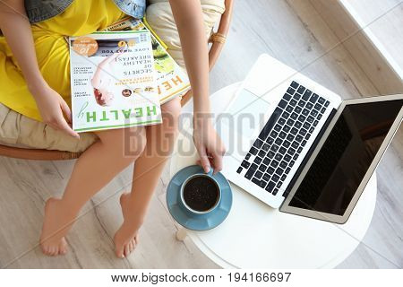 Woman with magazines and laptop on table