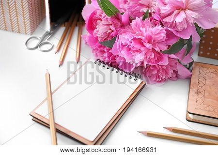 Bouquet of beautiful fragrant peony flowers and stationery on white background