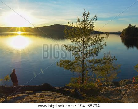 A man standing by a lake in sunset. Algonquin Provincial Park Ontario Canada