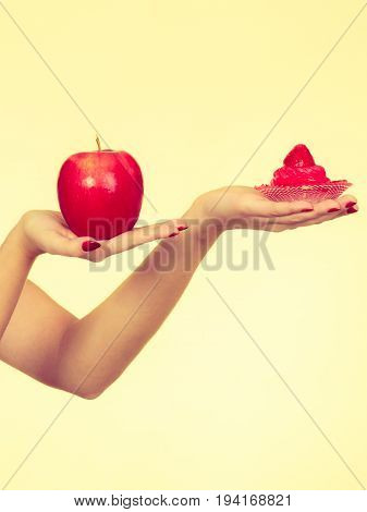 Woman Hand Holding Apple And Sweet Cupcake