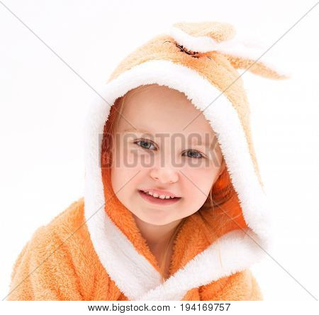Cute child smiling and wearing peachy bathrobe with lovely white bunny ears