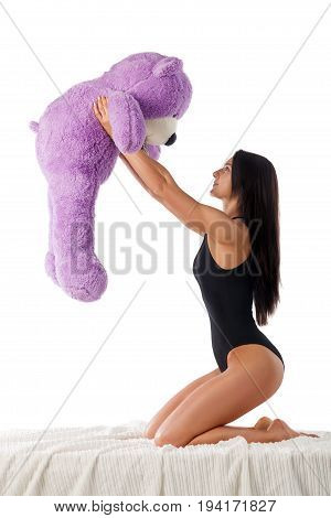 Beautiful brunette woman sitting on the bed. A woman is holding a teddy bear over her head. She smiles. Isolated. White background.