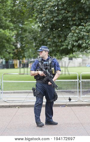 LONDON UNITED KINGDOM - JUNE 25 2017 : Metropolitan armed police officer during ceremonial changing of the London guards in front of the Buckingham Palace. This is one of the major attractions in London.