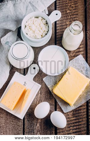 Fresh dairy product on kitchen wooden table. Cheese eggs milk cottage cheese yogurt cream and butter. Top view with copy space