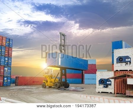 stacker holding container box at warehouse container in sunset sky background ,transportation and import export concept