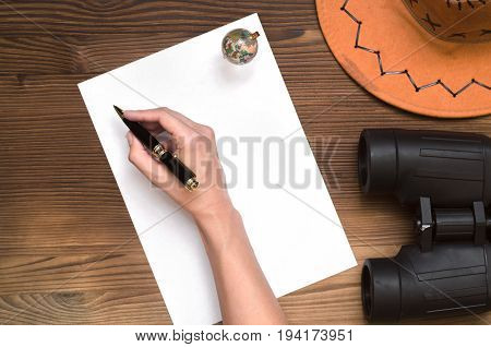 Hand with pen globe binoculars hat and blank paper page. Adventurer archeologist treasure hunt travel concept or education background mockup.