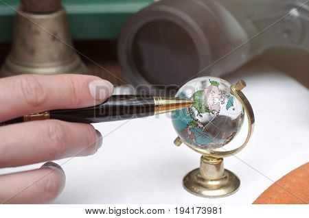 Female hand points to glass globe by pen binoculars book train conductor bell (teacher bell) money pen and blank page paper.. Adventurer traveler concept or education concept.