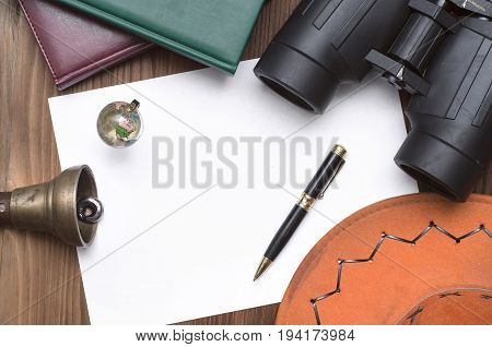Globe books binoculars train conductor bell (teacher bell) money pen cowboy hat and blank page paper on table. Adventurer treasure hunt traveler concept or education mockup background.