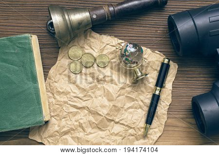 Adventurer treasure hunt travel concept or education mockup background. Globe book binoculars train conductor bell (teacher bell) money pen and blank crumpled brown page paper on table.