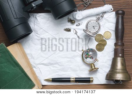 Globe book binoculars train conductor bell money pen pocket watch and blank page paper on table. Adventurer treasure hunt traveler concept or education background.