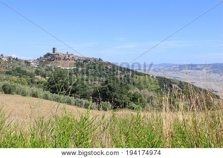 Ancient city fortress in the mountains in the Tuscany region, Italy, in the summer. Panoramic borough view from afar during a tourist trip