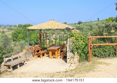 Wooden alcove with table and benches in summer. A place to rest in the heat in the mountains of the Tuscany region, Italy