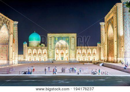 SAMARKAND UZBEKISTAN - AUGUST 29: Three madrassas of Registan illuminated and night with people in front. Registan is the most famous landmark of Uzbekistan. August 2016