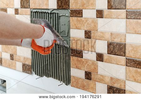 A tile's hand is holding a notched trowel and combing a adhesive for installation a tile.