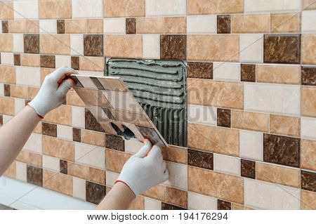 The tiler's hands are installing a tile with holes for electric boxes.