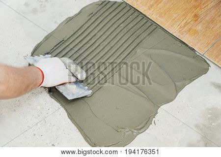 A tiler's hand is holding a notched trowel and combing a adhesive for laying a tile.