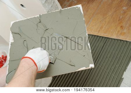 The tiler's hand is holding the trowel and putting the adhesive to the tile.