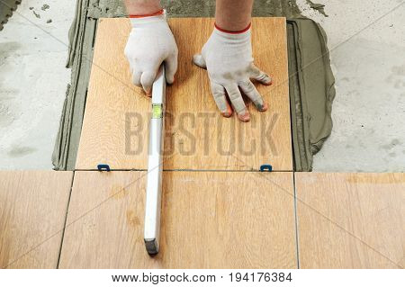 A tiler's hand is holding a construction level on a tile.