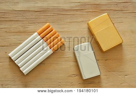 silver and gold lighter with cigarette on wooden board