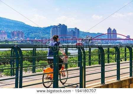 TAIPEI TAIWAN - MAY 29: This is scenic view of a man cycling on a riverside path onn the outskirts of Taipei on a hot sunny day on May 29 2017 in Taipei