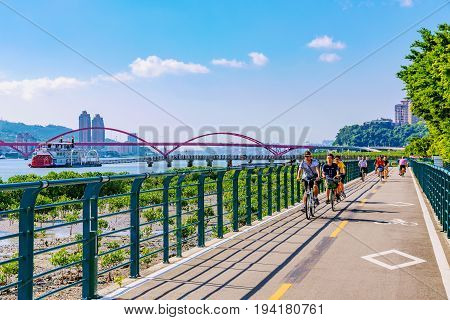 TAIPEI TAIWAN - MAY 29: This is a view of a riverside cycling path with people cycling and Guandu bridge in the background on a sunny day on May 29 2017 in Taipei