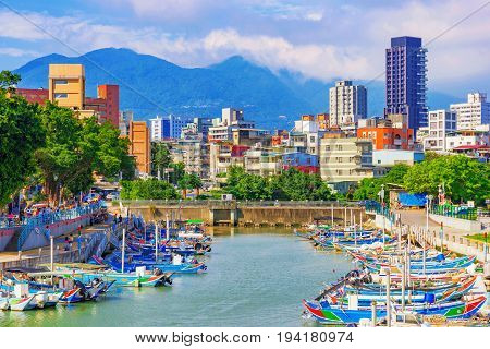 TAIPEI TAIWAN - MAY 29: This is view of Chung Kang fishing port and city buildings in the Guandu area on the outskirts of Taipei on May 29 2017 in Taipei