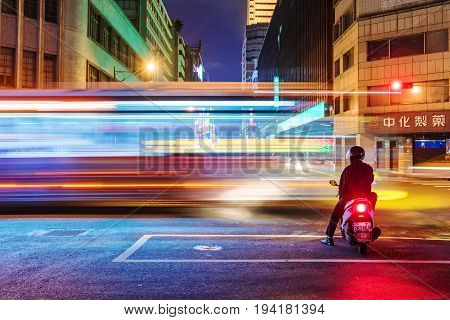 TAIPEI TAIWAN - MAY 27: This is a night view of motorcyclist waiting at traffic lights for the light to change to green in the downtown area on May 27 2017 in Taipei