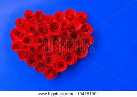 Red roses made of heart-shaped paper on a blue background.