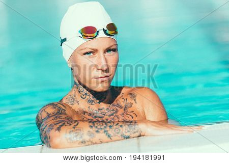 Portrait Of Female Swimmer With Tattoos Posing By The Swimming Pool