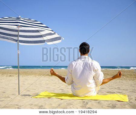 Man doing meditation on beach on towel