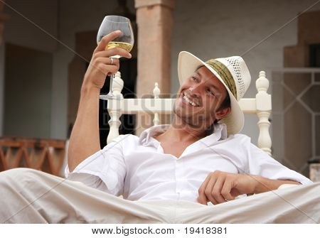 Smiling man sitting outdoor with glass of white wine
